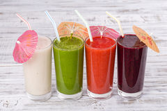 Fresh avocado, strawberry, blueberry and banana drinks on wooden table, assorted protein cocktails with fresh fruits. Stock Photography