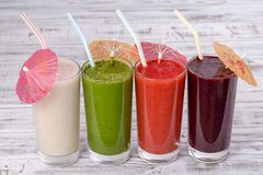 Fresh avocado, strawberry, blueberry and banana smoothie on white wooden table, assorted protein cocktails with fresh fruits. Four. Fresh avocado, strawberry Stock Photos