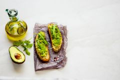 Avocado toasts with arugula. Fresh avocado toasts with arugula close up. Good fats raw healthy eating concept royalty free stock images