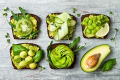 Fresh avocado toasts with different toppings. Healthy vegetarian breakfast with rye wholegrain sandwiches. Fresh avocado toasts with different toppings. Healthy stock photos