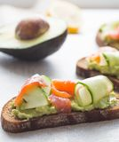 Fresh avocado toasts with red fish salmon and cucumber . Healthy vegetarian breakfast with rye wholegrain sandwiches royalty free stock photo