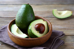 Fresh avocado in a wooden bowl royalty free stock images