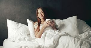 Sunny start of day. Fresh awakening young woman holding coffee cup while sitting in the bed, sunny morning start of the day stock footage