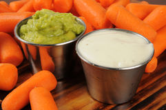 Fresh baby carrots with dips Royalty Free Stock Images
