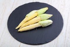Fresh baby corn. Heap on the wood background Stock Photo