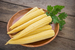 Fresh baby corn on wooden plate Stock Photo
