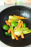 Fresh baby vegetables being sauteed Stock Photo