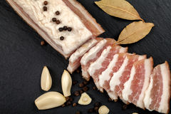 Fresh bacon with garlic and peppercorns, bay leaf. Ukrainian traditional cuisine. On the slate surface Stock Photo
