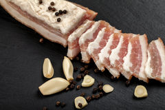 Fresh bacon with garlic and peppercorns. Ukrainian traditional cuisine. On the slate surface Stock Images