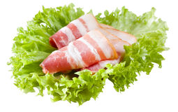 Fresh bacon on salad leaves. Isolated on white background Royalty Free Stock Images