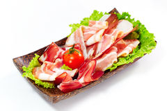 Fresh bacon stripes served with greens and tomato. On white. Fresh bacon stripes served with greens and tomato on wooden plate. On white background. Bright Royalty Free Stock Image