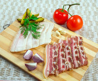 Fresh bacon with on wooden table. Fresh bacon with vegetables cucumber, tomato and garlic on a wooden platter, sliced Stock Image