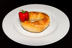 Fresh bagel on a plate with small red pepper Royalty Free Stock Photos