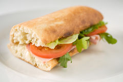 Fresh baguette. On white plate with tomatoes, challenge and a slice of ham, detail Royalty Free Stock Image