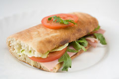 Fresh baguette. On white plate with tomatoes, challenge and a slice of ham royalty free stock photography