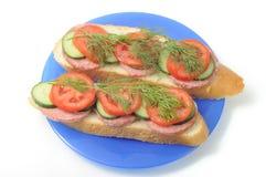 Fresh baguette sandwich. On blue plate Stock Photography