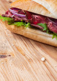 Fresh baguette with sliced roast beef and herbs Stock Photography