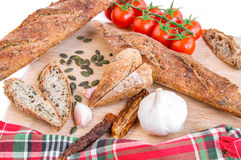 Fresh baguettes, tomatoes, garlic, pumpkin seeds on wooden cutti Royalty Free Stock Images
