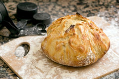 Fresh baked artisan bread. Freshly baked artisan bread on a marble background and cutting board with flour Stock Images