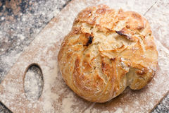 Fresh baked artisan bread. Freshly baked artisan bread on a marble background and cutting board with flour Stock Image