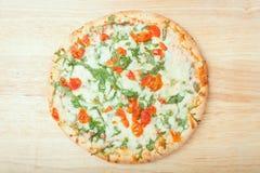 Fresh baked arugula pizza on wooden background Stock Photo