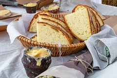 Fresh baked bread a piece of a large loaf rustic appetizing breakfast in a basket wicker with yellow honey stock images