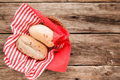 Fresh baked buns in basket on wooden background. Two fresh bread buns in the basket on wooden table, top view. Food background. Free space for text, menu photo Royalty Free Stock Images