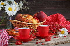 Fresh baked buns with a cup of coffee. On rustic wooden background Stock Photos