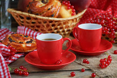 Fresh baked buns with a cup of coffee. On rustic wooden background Stock Image