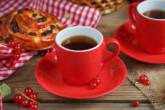 Fresh baked buns with a cup of coffee. On rustic wooden background Royalty Free Stock Photo