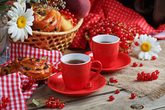 Fresh baked buns with a cup of coffee. On rustic wooden background Stock Photo