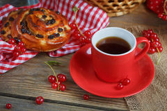 Fresh baked buns with a cup of coffee. On rustic wooden background Royalty Free Stock Photos