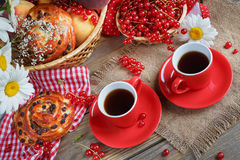 Fresh baked buns with a cup of coffee. On rustic wooden background Royalty Free Stock Photography