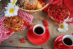 Fresh baked buns with a cup of coffee. On rustic wooden background Royalty Free Stock Image