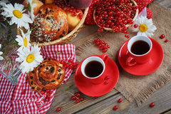 Fresh baked buns with a cup of coffee. On rustic wooden background Royalty Free Stock Images