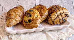 Fresh baked buns on plate over napkin. Close-up of french pastry with croissant and buns with raisin and chocolate on plate over napkin Stock Photography