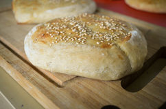 Fresh baked buns with sesame. On wooden plate Royalty Free Stock Photography