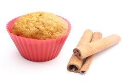 Fresh baked carrot muffin and cinnamon sticks. White background Stock Photo