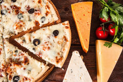 Fresh baked cheese pizza with olives, fast food. Appetizing hot pizza served on rustic wooden table with cheese assortment, parsley and cherry tomatoes, flat lay Royalty Free Stock Photos