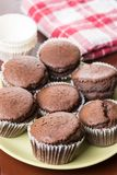 Fresh baked chocolate cup cakes served on the plate with kitchen dishtowel in the background Stock Photography