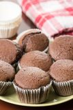 Fresh baked chocolate cup cakes served on the plate with kitchen dishtowel in the background Royalty Free Stock Image