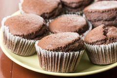 Fresh baked chocolate cup cakes served on the plate with kitchen dishtowel in the background Stock Photos