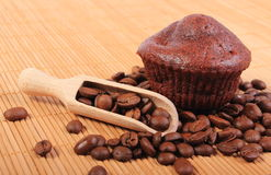 Fresh baked chocolate muffins and coffee grains Royalty Free Stock Photos