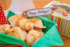 Fresh baked coconut macaroons with seasons greeting tag. Royalty Free Stock Images