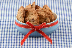 Fresh baked cookies. Fresh baked oatmeal and raisin cookies in blue bowl with red ribbon on checked cloth background Stock Photography