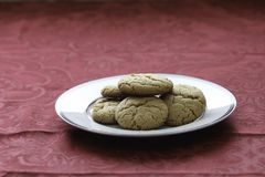 Homemade peanut butter cookies on white plate. Fresh baked cookies. close up showing texture. Plate on table with red tablecloth Royalty Free Stock Image