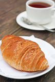Fresh-baked croissant and cup of tea Royalty Free Stock Image
