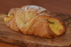 Fresh baked croissant with vanilla filling. Royalty Free Stock Images