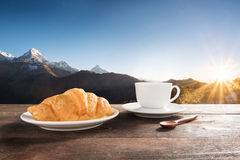 Fresh baked croissants and coffee on a wooden table at mountain Royalty Free Stock Image
