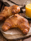 Fresh baked Croissants. Some fresh baked Croissants on rustic wooden background Stock Photography